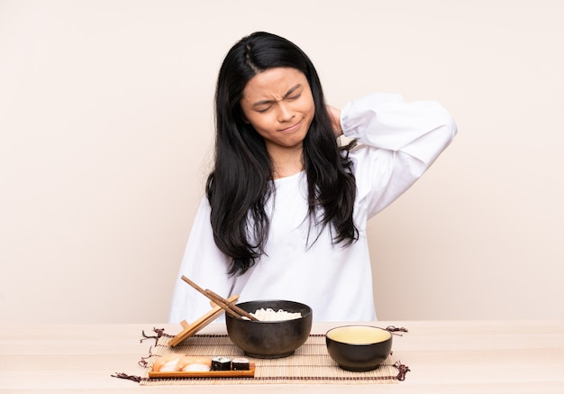 Ragazza asiatica dell'adolescente che mangia alimento asiatico isolato su fondo beige con il mal di collo