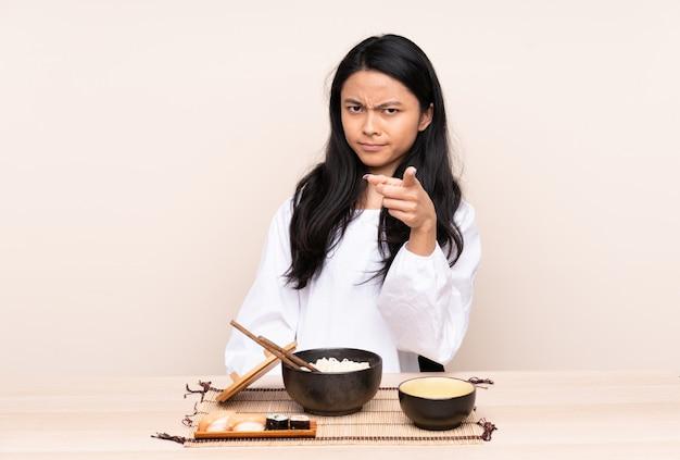 Ragazza asiatica dell'adolescente che mangia alimento asiatico sulla parete beige frustrata e che indica la parte anteriore