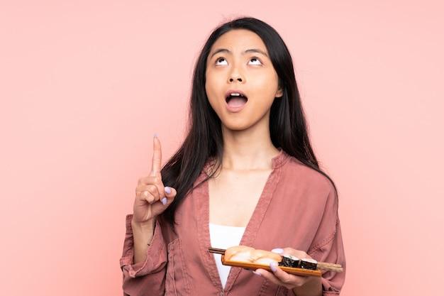 Ragazza asiatica dell'adolescente che mangia i sushi isolati sul rosa