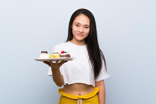 Ragazza asiatica dell'adolescente che tiene i lotti di mini torte differenti che sorridono molto