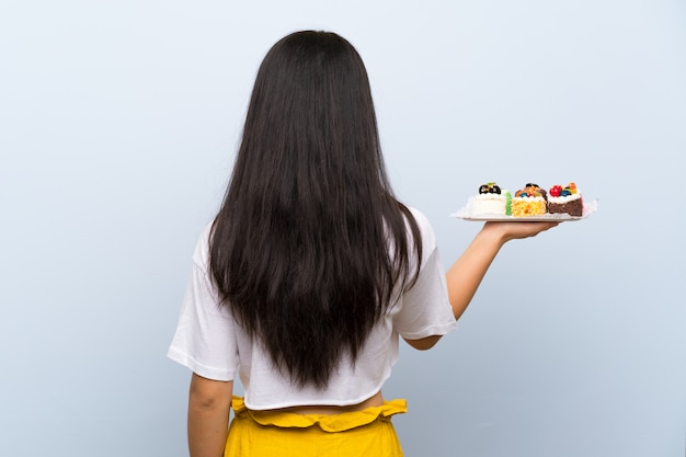Ragazza asiatica dell'adolescente che tiene i lotti di mini torte differenti nella posizione posteriore