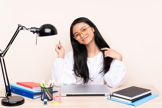 Ragazza asiatica dell'allievo in un posto di lavoro con un computer portatile isolato sul beige