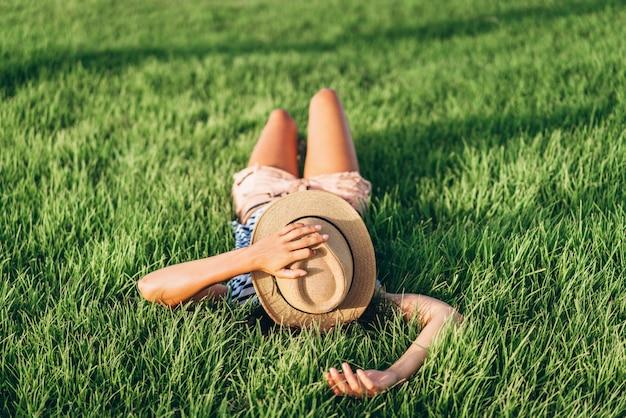 Ragazza asiatica della stalla turistica felice e stanca sveglia che riposa all'aperto sull'erba.