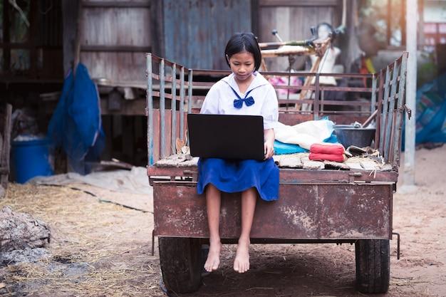 Ragazza asiatica dello studente uniforme che utilizza il taccuino del computer nella campagna della tailandia