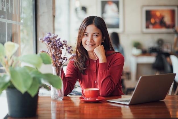 Ragazza asiatica di affari che lavora e che beve caffè in caffè con il computer portatile