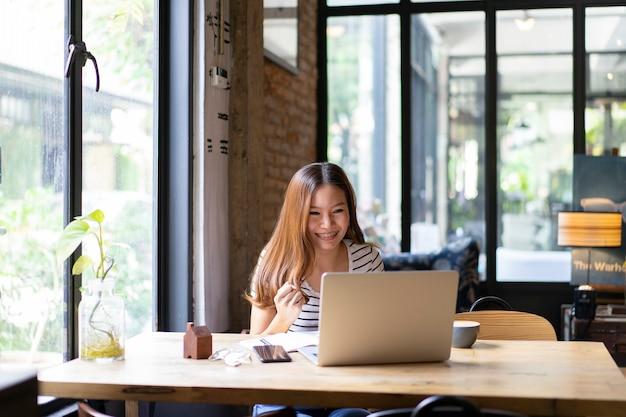 Ragazza asiatica di affari felice e iniziare a lavorare con il computer portatile al caffè