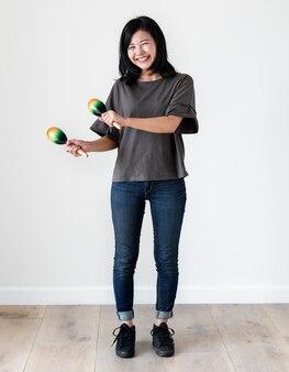 Ragazza asiatica di etnia che gioca macaras