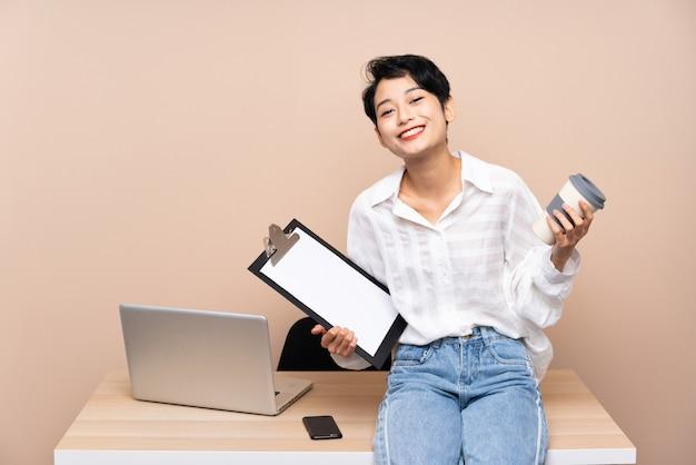 Ragazza asiatica di giovani affari nel suo luogo di lavoro