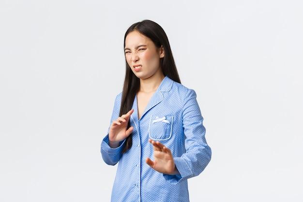 Ragazza asiatica distrutta e scontenta in pigiama blu allunga le mani in avanti in segno di rifiuto, rifiutando qualcosa di disgustoso, facendo smorfie di avversione e antipatia, stringendo la mano in segno di diniego sul muro bianco