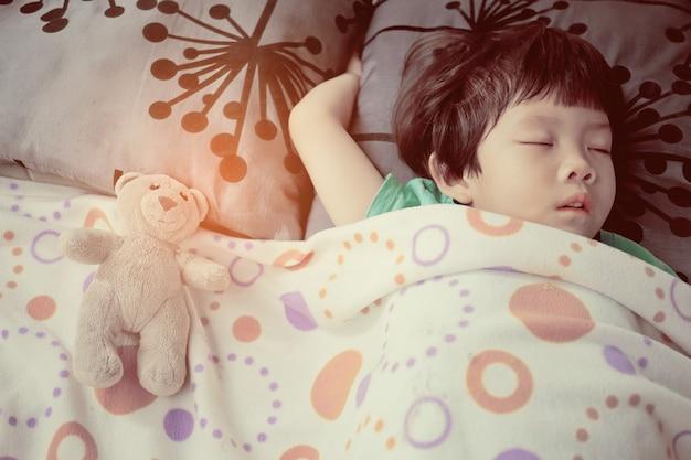 Ragazza asiatica dormire sul letto, bambino malato, sonno bambino