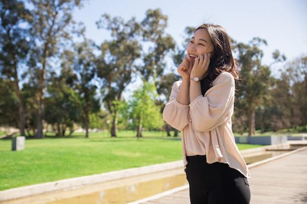 Ragazza asiatica emozionante che parla sulla cellula e ridendo