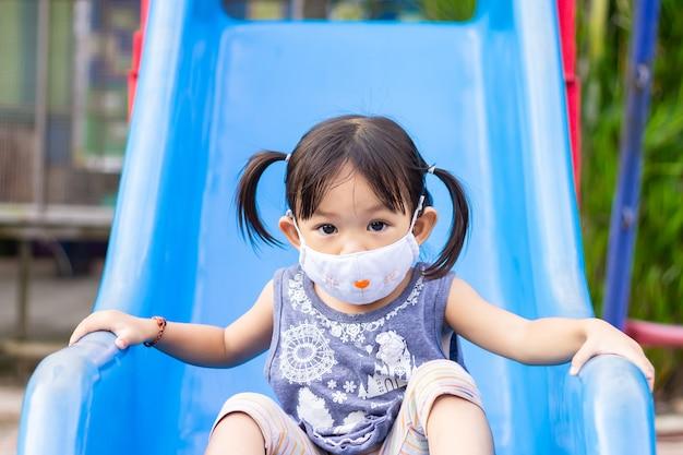 Ragazza asiatica felice del bambino che sorride e maschera del tessuto d'uso, lei che gioca con il giocattolo della barra del cursore al parco giochi