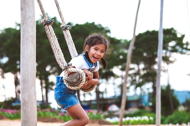 Ragazza asiatica felice del bambino divertendosi per giocare sulle oscillazioni di legno in campo da giuoco con la bella natura