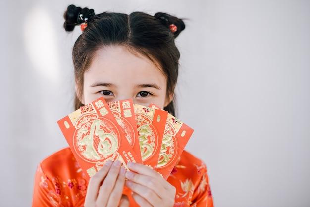 Ragazza asiatica felice del nuovo anno cinese che tiene le buste rosse