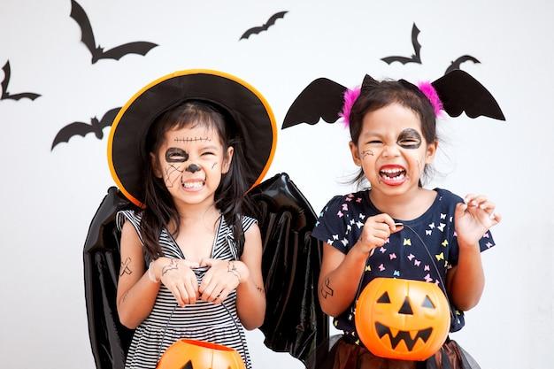 Ragazza asiatica felice del piccolo bambino in costumi e trucco divertendosi sulla celebrazione di halloween