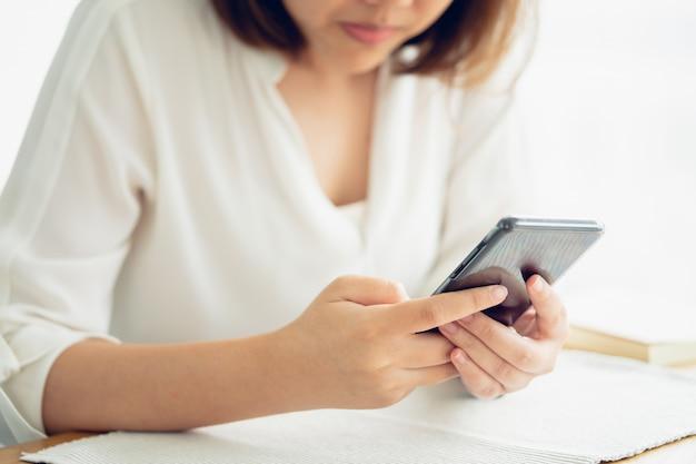 Ragazza asiatica gioca a smartphone per l'intrattenimento e il lavoro fuori dall'ufficio