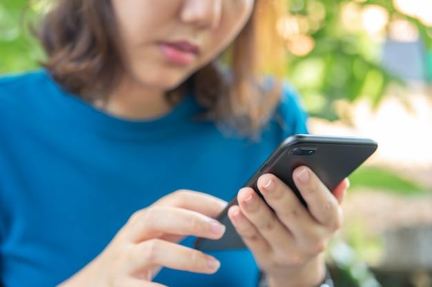 Ragazza asiatica gioca smartphone per l'intrattenimento e il lavoro fuori dall'ufficio o fuori.