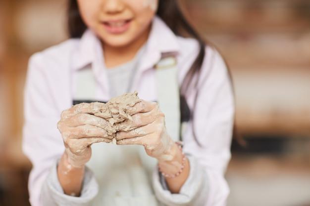 Ragazza asiatica impastare argilla