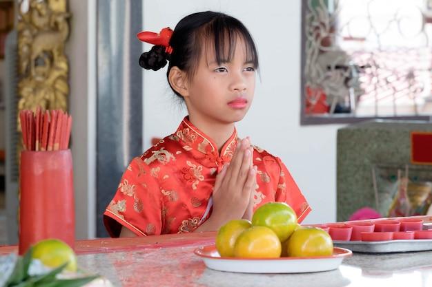 Ragazza asiatica in abito cinese pagando rispetto a dio.