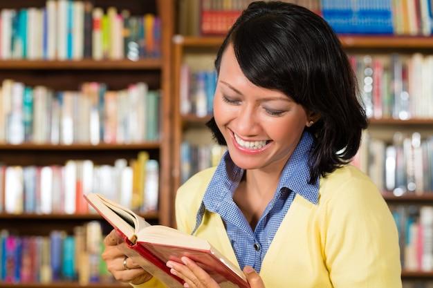 Ragazza asiatica in biblioteca che legge un libro