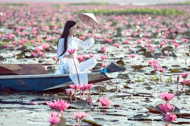 Ragazza asiatica in costume nazionale del vietnam che si siede sulla barca nel mare di loto rosso in undon thani, tailandia.