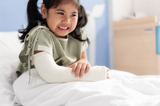 Ragazza asiatica in ospedale sdraiato sul letto male con un braccio rotto