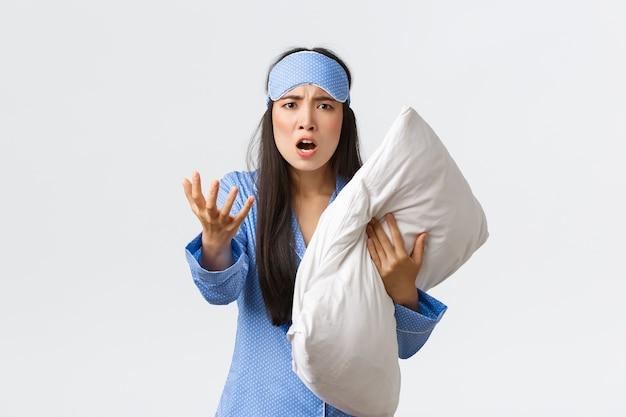 Ragazza asiatica infastidita arrabbiata con insonnia, indossando la maschera per dormire e il pigiama
