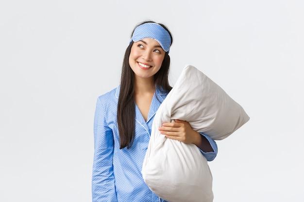 Ragazza asiatica kawaii astuta e premurosa in pigiama blu e maschera per dormire, tenendo in mano il cuscino e guardando curioso nell'angolo in alto a sinistra, sorridendo sorniona come se avesse un'idea, immaginando qualcosa, muro bianco