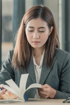 Ragazza asiatica leggendo un libro sulla scrivania.