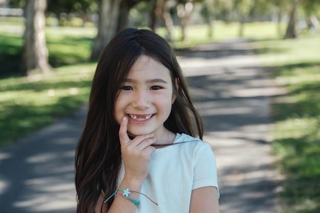 Ragazza asiatica mista felice che manca i suoi denti da latte anteriori che sorridono con sicuro nel parco, salute orale del bambino e cure odontoiatriche