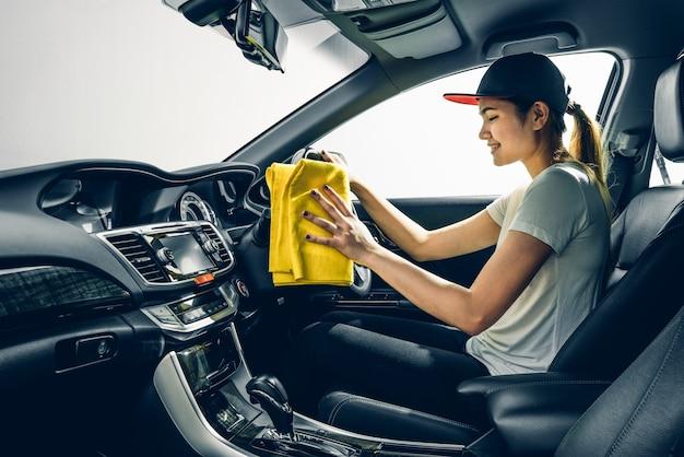 Ragazza asiatica pulisca l'automobile moderna della console, interna nera