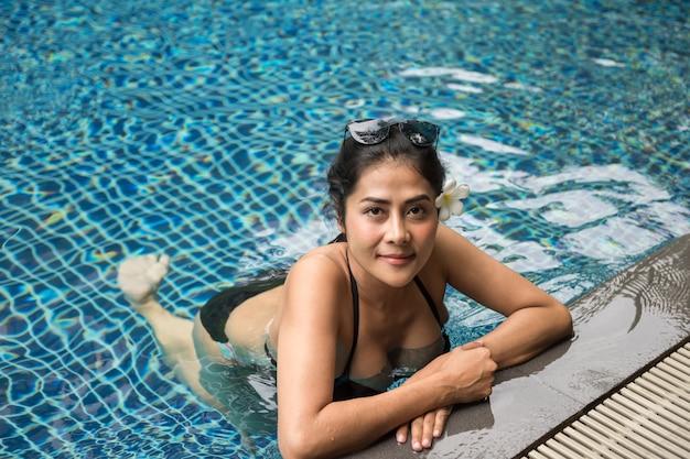 Ragazza asiatica sexy del bikini nella piscina blu