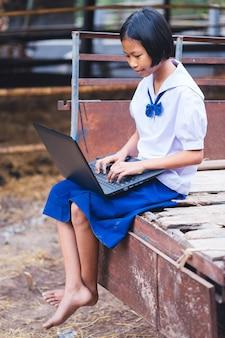 Ragazza asiatica studentessa uniforme utilizzando il notebook del computer