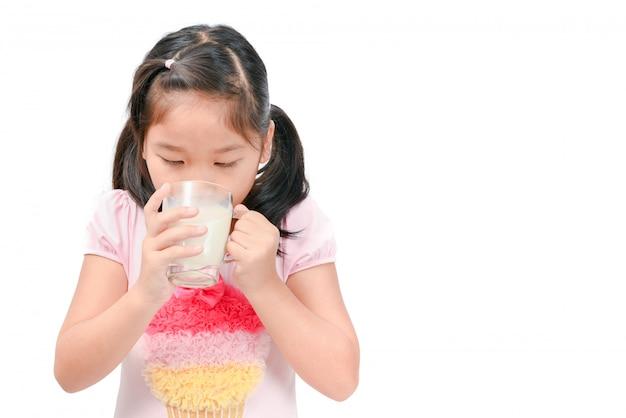 Ragazza asiatica sveglia che beve latte fresco isolato