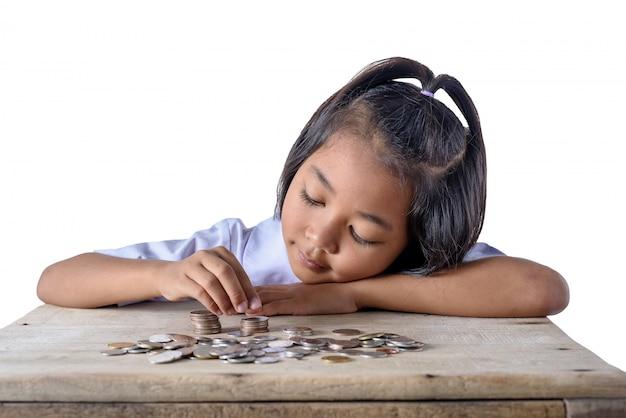 Ragazza asiatica sveglia che conta e monete del mucchio per il risparmio isolato su fondo bianco