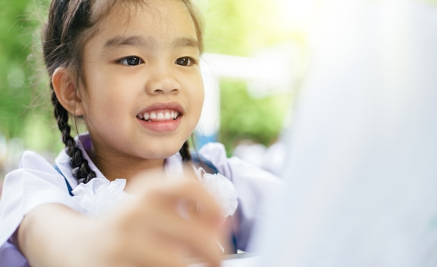 Ragazza asiatica sveglia che legge un libro e denti sorridenti bianchi