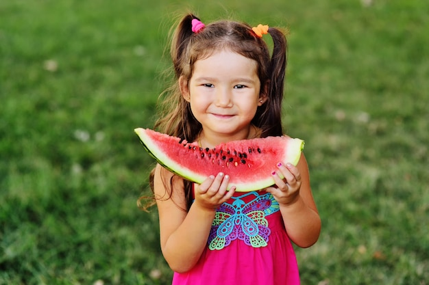 Ragazza asiatica sveglia che mangia anguria succosa e sorridere