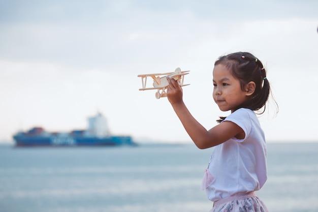 Ragazza asiatica sveglia del bambino che gioca con l'aeroplano di legno del giocattolo nella spiaggia con felicità