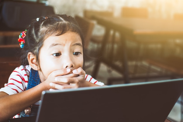 Ragazza asiatica sveglia del bambino che guarda computer portatile e che fa fronte emozionante nel caffè