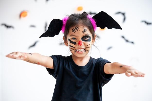 Ragazza asiatica sveglia del bambino che indossa i costumi e il trucco di halloween divertendosi sulla celebrazione di halloween