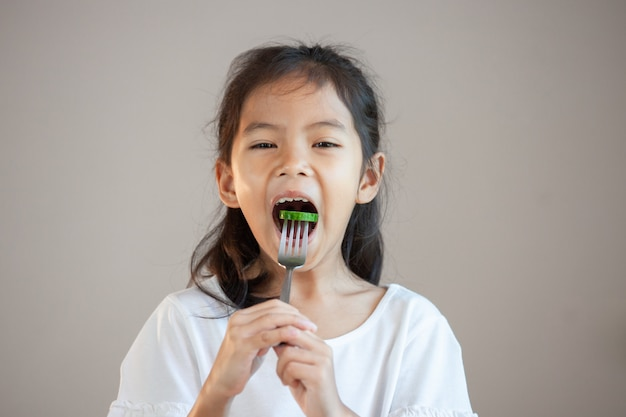 Ragazza asiatica sveglia del bambino che mangia le verdure sane con la forcella