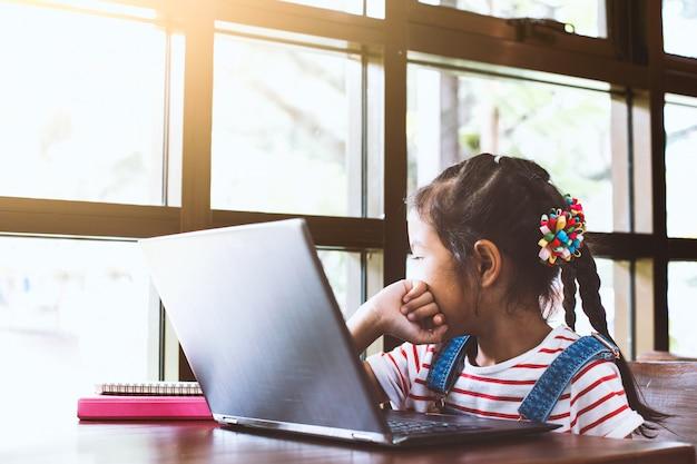 Ragazza asiatica sveglia del bambino che per mezzo del computer portatile e guardando fuori nel caffè