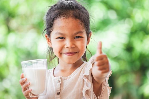 Ragazza asiatica sveglia del bambino che tiene bicchiere di latte e fa il forte gesto