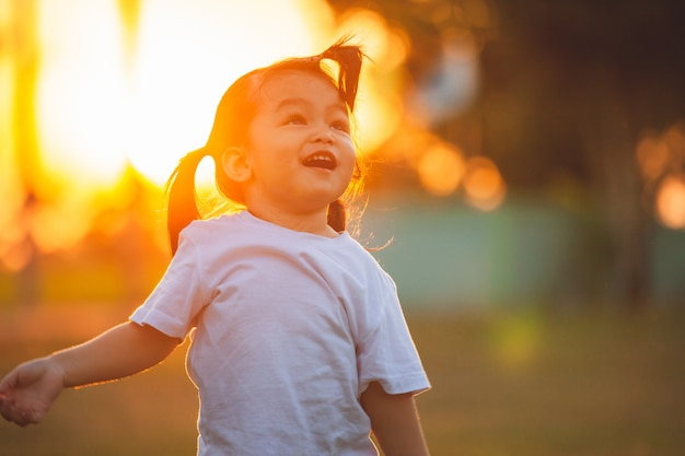 Ragazza asiatica sveglia del piccolo bambino che cammina e che gioca nel parco al tempo di tramonto con divertimento e felicità