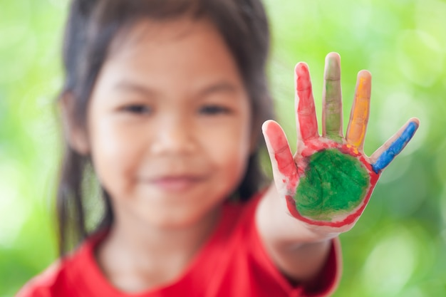 Ragazza asiatica sveglia del piccolo bambino con le mani dipinte che mostrano le dita numero cinque