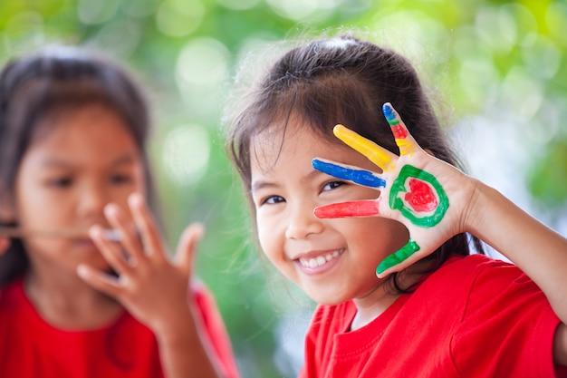 Ragazza asiatica sveglia del piccolo bambino con le mani dipinte che sorride con il divertimento e la felicità