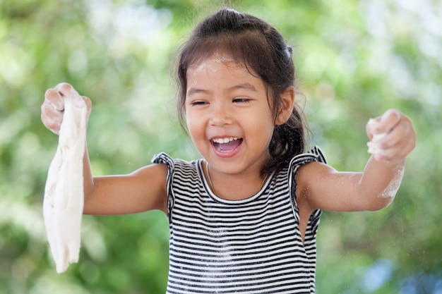 Ragazza asiatica sveglia del piccolo bambino divertendosi per preparare una pasta per i biscotti bollenti