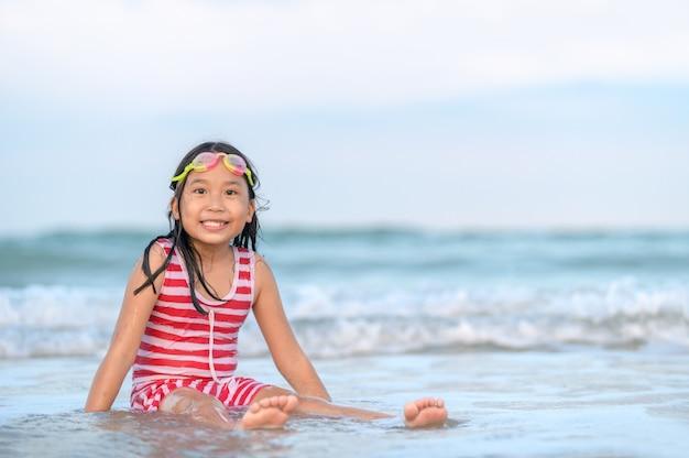 Ragazza asiatica sveglia felice che gioca onda sulla spiaggia,