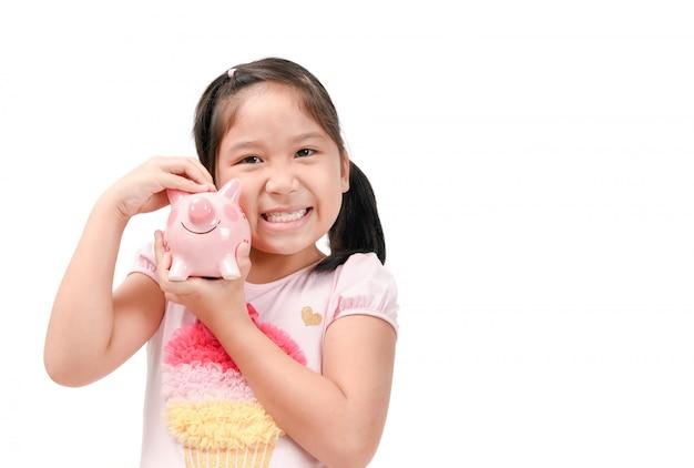 Ragazza asiatica sveglia felice che tiene porcellino salvadanaio rosa
