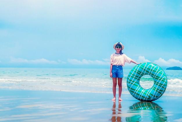 Ragazza asiatica sveglia sull'anello di nuotata della tenuta della spiaggia del mare di estate
